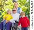 Two little kid boys, their grandmother and grandfather in wheelchair in summer garden. Happy family of four spending time together, outdoors. - stock photo