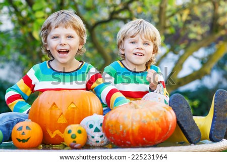Two little kid brother boys making jack-o-lantern for halloween in autumn garden, outdoors. Happy family having fun together - stock photo