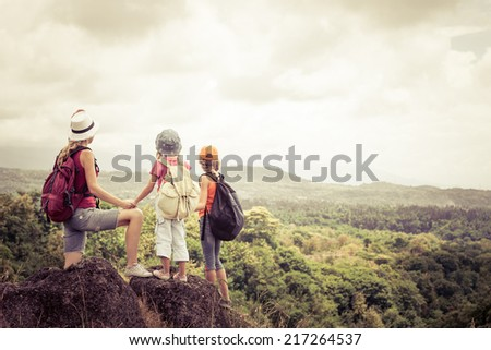two little kids and mother standing on the mountain at the day time