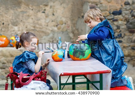 Two little kids, boy and girl on a harvest festival, painting with colors a pumpkin. Children celebrating traditional festival halloween or thanksgiving. - stock photo