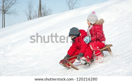 Two little kids - boy and girl - sliding with sledge in the snow.