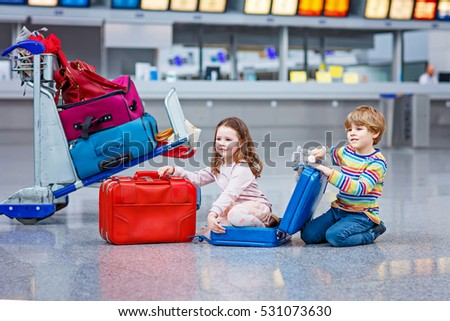 Two little kids, boy and girl with suitcases at the airport, indoors and waiting for going on family vacations. Happy children, twins, brother and sister exciting about a flying with airplane.