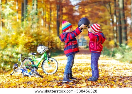 Two little kids boys, best friends in autumn forest. Older brother helping younger child to put his bike helmet. Happy siblings with bicycles. - stock photo