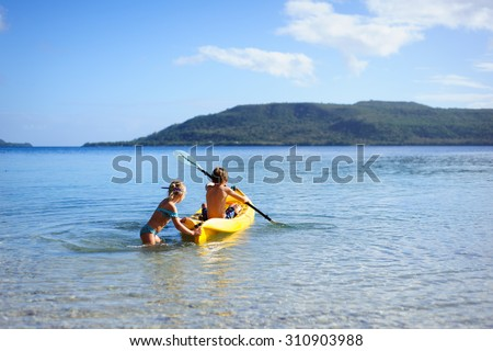 Two little kids- brother and sister kayaking in the ocean on a yellow kayak - stock photo