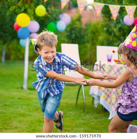 Two little kids celebrating birthday dancing roundelay - stock photo