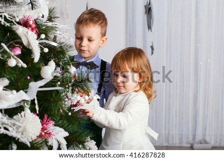 Two little kids decorating Christmas tree with toys, flowers and balls. New year preparation. Happy children and family. - stock photo