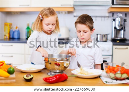 Two little kids helping at kitchen with salad making - stock photo