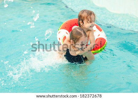 two little kids playing in the pool - stock photo