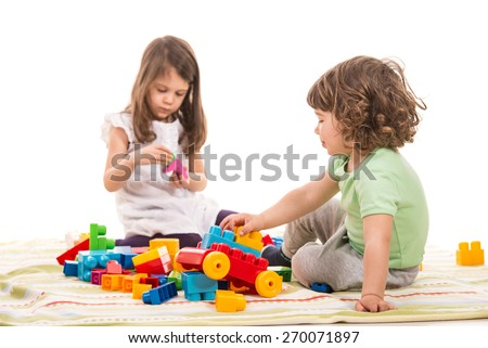 Two little kids playing with bricks home isolated on white background