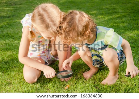 Two little kids  playing with magnifying glass outdoors in the day time - stock photo