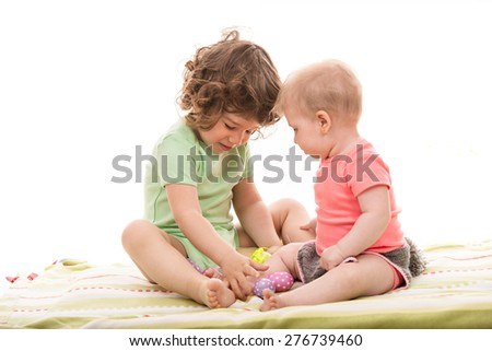Two little kids,toddler boy and baby girl playing with Easter eggs on a blanket - stock photo