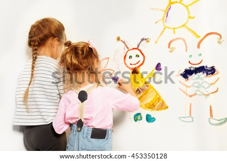 Two little painters drawing at the wall - stock photo