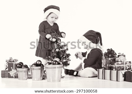 two little  santa helpers decorating a tree