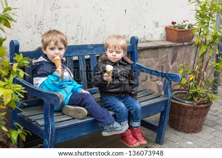 Two little sibling boys eating ice cream in cone - stock photo