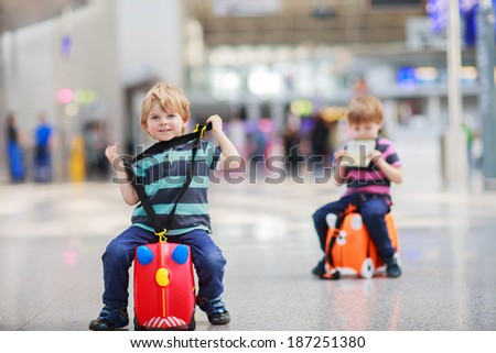 Two little sibling boys having fun and going on vacations trip with suitcase at airport, indoors. - stock photo