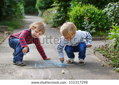 Two little sibling boys painting with chalk outdoors in summer - stock photo