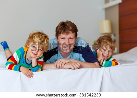 Two little sibling kid boys and their dad having fun in bed after sleeping at home, indoor. Brothers and father smiling at the camera. Family, vacation, childhood concept - stock photo