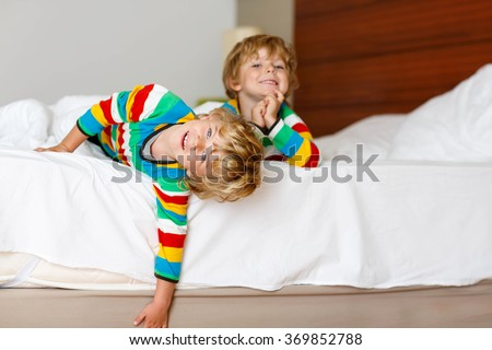 Two little sibling kid boys having fun in bed after sleeping at home, indoor. Brothers smiling at the camera. Family, vacation, childhood concept. Selective focus on one child - stock photo
