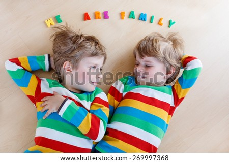 Two little sibling kid boys having fun together, indoors. Blond twins of 3 years in colorful shirts laughing and smiling. Family concept. - stock photo