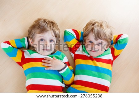 Two little sibling kid boys having fun together, indoors. Children in colorful shirts laughing and smiling. Family concept. - stock photo