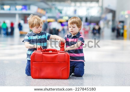 Two little sibling twins having fun and going on vacations trip with suitcase at airport, indoors. Kids packing red suitcase.