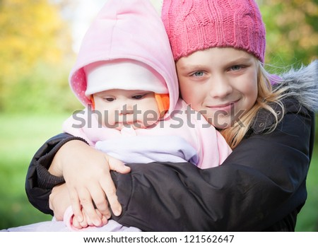 Two little sister girls in the park. Outdoor portrait
