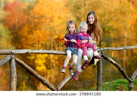 Two little sisters and their mom having fun in autumn park - stock photo