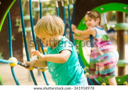 Two  little sisters at action-oriented playground in summer park