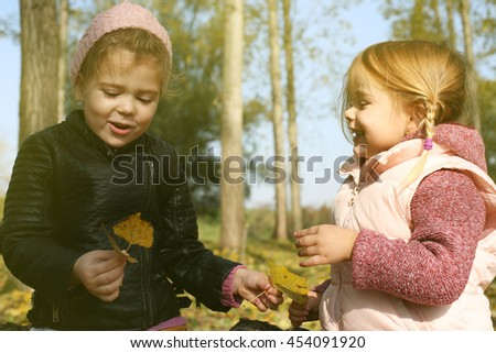 Two little sisters communicate in the park.