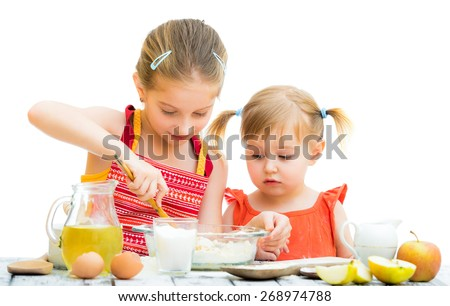 two little sisters cooking isolated on a white background - stock photo