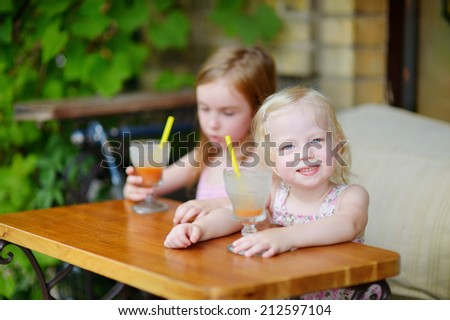 Two little sisters drinking orange juice in an outdoor cafe on warm and sunny summer day - stock photo