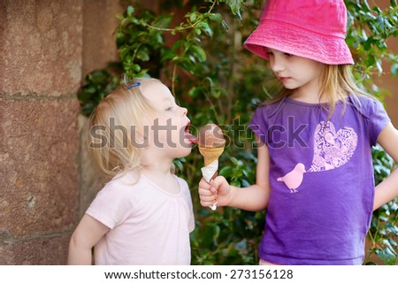 Two little sisters eating ice cream outdoors - stock photo