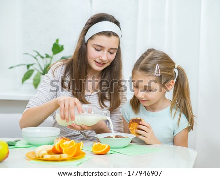Two little sisters eating muesli with fresh fruits