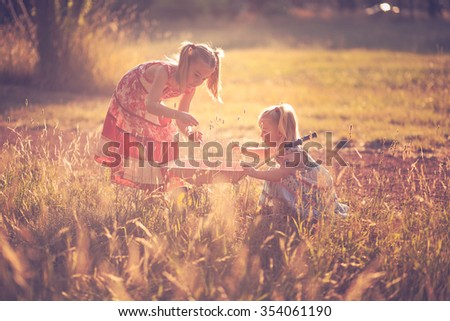 Two little sisters enjoying playing in nature - stock photo