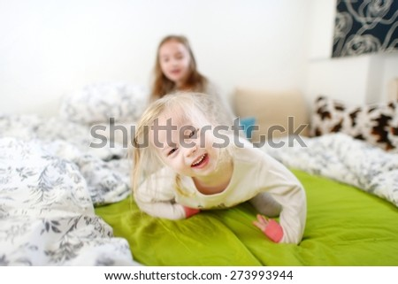 Two little sisters fooling around, playing and having fun in bed on sunny sunday morning - stock photo