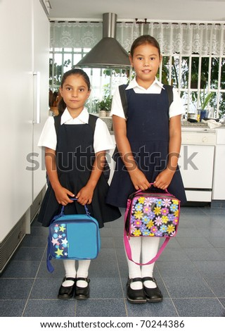 Two little sisters going to school. - stock photo