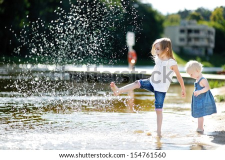 Two little sisters having fun by a river at summer - stock photo