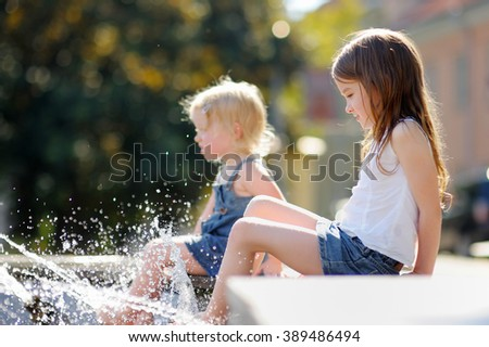 Two little sisters having fun in a city fountain  - stock photo