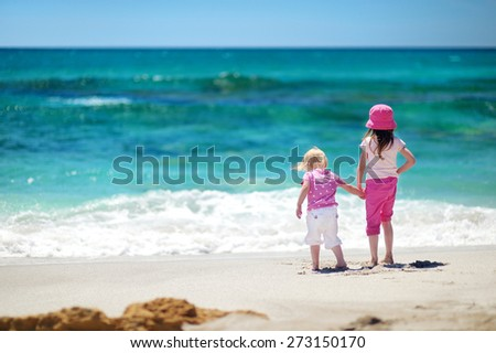 Two little sisters having fun on a sandy beach on Sardinia - stock photo