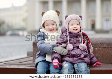 Two little sisters having fun on winter day in a city - stock photo