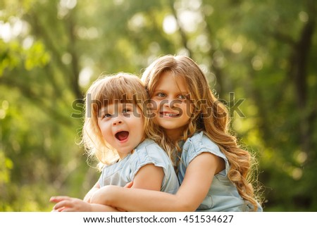 Two little sisters hug. Park on a sunny summer day. Family time. Cute babies