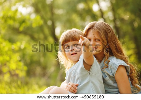 Two little sisters hug. Park on a sunny summer day. Family time. cute babies. Younger shows forefinger away