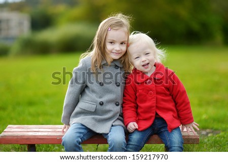 Two little sisters hugging on a bench on autumn day