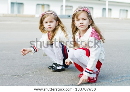 two little sisters in clothes in a nautical theme and a ship in
