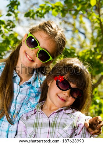 Two little sisters in sunglasses posing outdoor - stock photo