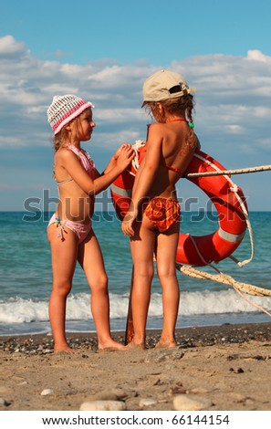 two little sisters in swimsuits standing on beach near metal pole, on pole hanging red life buoy