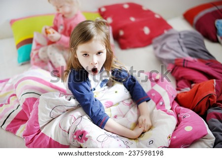 Two little sisters playing in bed on sunny morning - stock photo