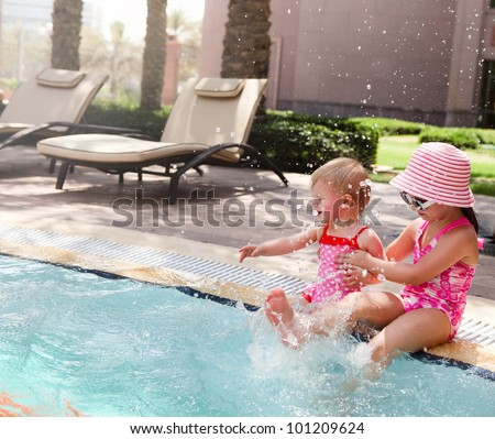 Two little sisters playing in water in swimming pool - stock photo