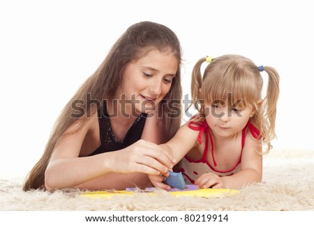 two little sisters playing on a carpet