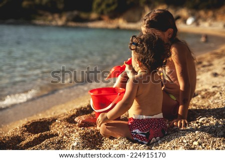 Two little sisters playing with sand on the beach - stock photo